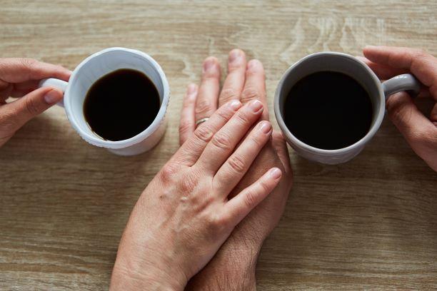2 paar hände auf dem tisch, zwei Tassen mit Kaffee oder Tee, zwei Hände berühren sich